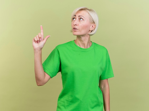 인상적인 중년 금발 슬라브 여자가 머리를 옆으로 돌리고 복사 공간이있는 올리브 녹색 벽에 고립 된 가리키는