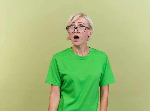복사 공간 올리브 녹색 벽에 고립 찾고 안경을 쓰고 감동 중년 금발 슬라브 여자
