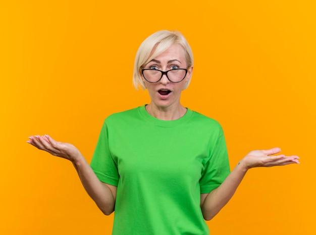 노란색 벽에 고립 된 전면을보고 빈 손을 보여주는 안경을 쓰고 감동 중년 금발 슬라브 여자