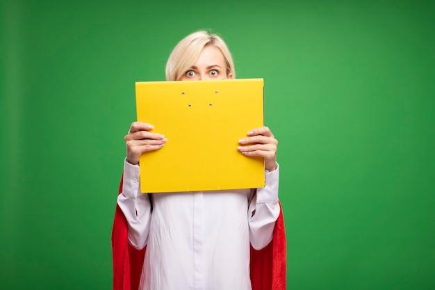 복사 공간이 있는 녹색 벽에 격리된 뒤에서 닫힌 폴더를 들고 빨간 망토를 입은 중년 금발 슈퍼히어로 여성