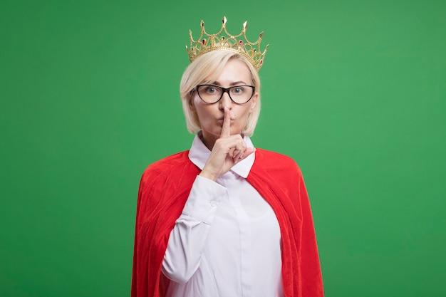 沈黙のジェスチャーをしている眼鏡と王冠を身に着けている赤いマントで感銘を受けた中年の金髪のスーパーヒーローの女性