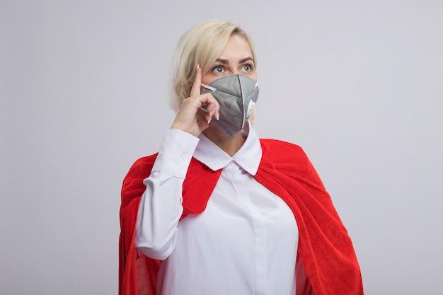 コピースペースで白い壁に分離された思考ジェスチャーをしている側を見て保護マスクを身に着けている赤いマントで感銘を受けた中年の金髪のスーパーヒーローの女性