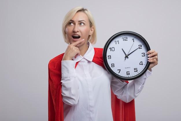 Donna bionda di mezza età impressionata del supereroe in mantello rosso che tiene l'orologio che mette la mano sul mento che esamina lato isolato sulla parete bianca con lo spazio della copia