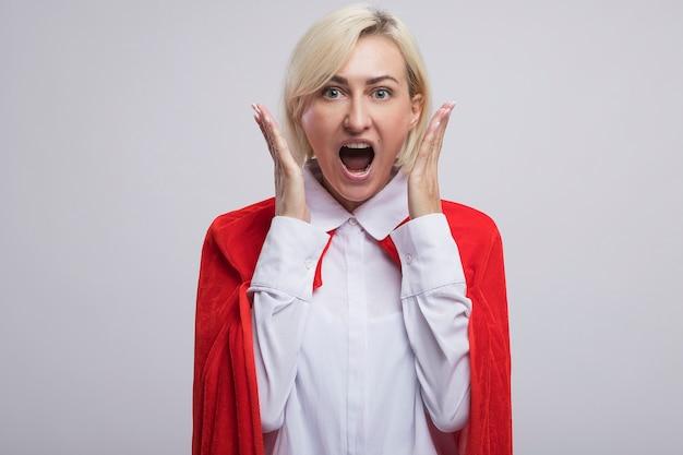 Donna bionda di mezza età impressionata del supereroe in mantello rosso che tiene le mani vicino alla testa guardando la parte anteriore isolata sulla parete bianca con lo spazio della copia