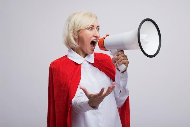 Donna bionda di mezza età impressionata del supereroe in mantello rosso che grida nell'altoparlante che guarda il lato che mostra la mano vuota isolata sulla parete bianca