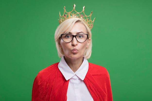 Donna supereroe bionda di mezza età impressionata in mantello rosso che indossa occhiali e corona che fa gesto di bacio