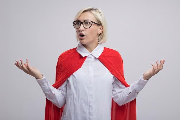 Donna bionda di mezza età impressionata del supereroe in capo rosso con gli occhiali guardando il lato che mostra le mani vuote isolate sul muro bianco