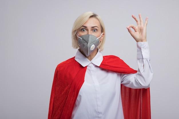 Donna bionda di mezza età impressionata del supereroe in mantello rosso che indossa maschera protettiva che guarda davanti facendo segno giusto isolato sulla parete bianca con lo spazio della copia