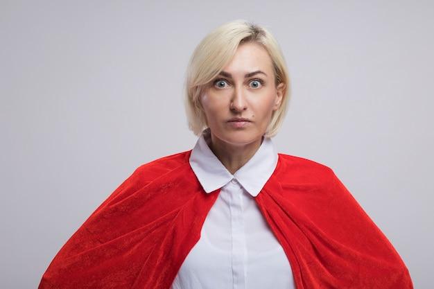 Donna supereroe bionda di mezza età impressionata in mantello rosso