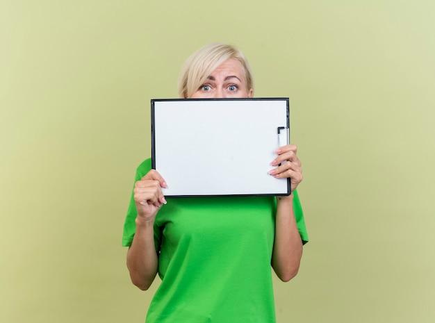 Впечатленная блондинка средних лет, держащая буфер обмена перед ртом, смотрящая вперед сзади, изолированная на оливково-зеленой стене
