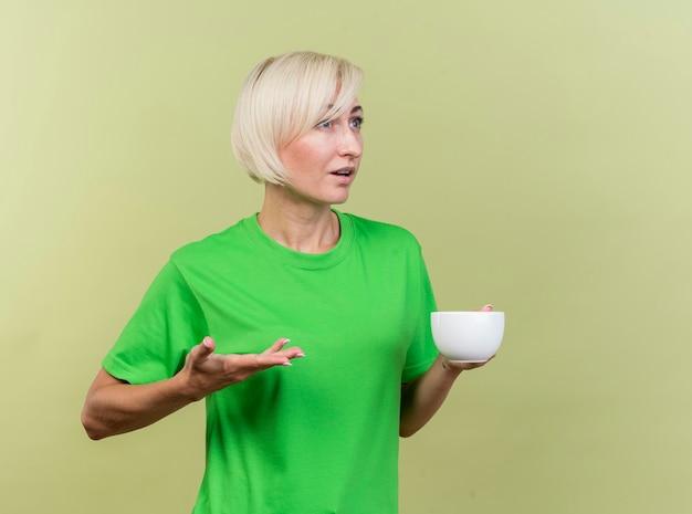 올리브 녹색 벽에 똑바로 고립 찾고 빈 손을 보여주는 차 한잔을 들고 감동 중년 금발의 여자