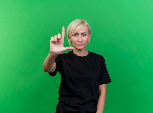Впечатленная блондинка средних лет, смотрящая вперед, делает жест неудачника, изолированного на зеленой стене