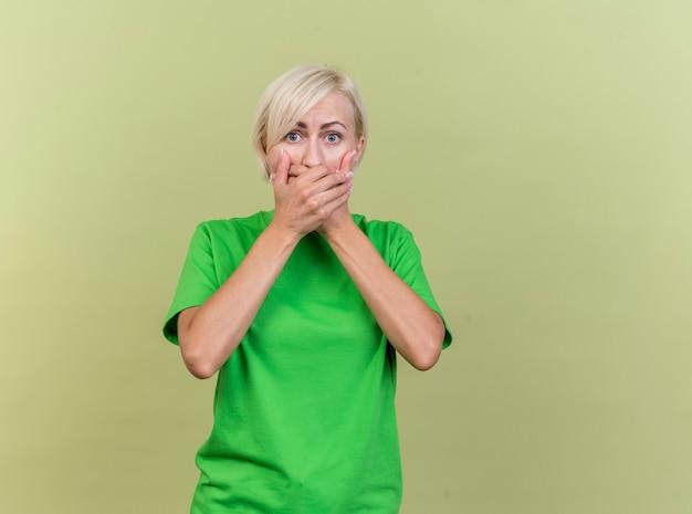 Впечатленная блондинка средних лет, смотрящая вперед, делает секретный жест, изолированный на оливково-зеленой стене