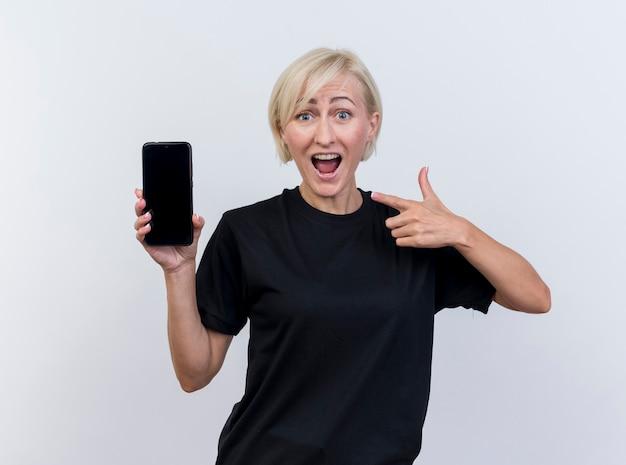 흰색 벽에 고립 된 전면을보고 그것을 가리키는 휴대 전화를 보여주는 감동 중년 금발의 여자