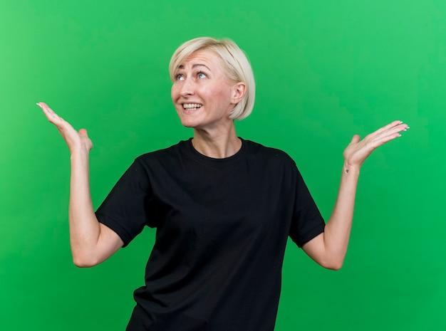 녹색 벽에 고립 된 빈 손을 보여주는 찾고 머리를 옆으로 돌리는 감동 중년 금발의 여자