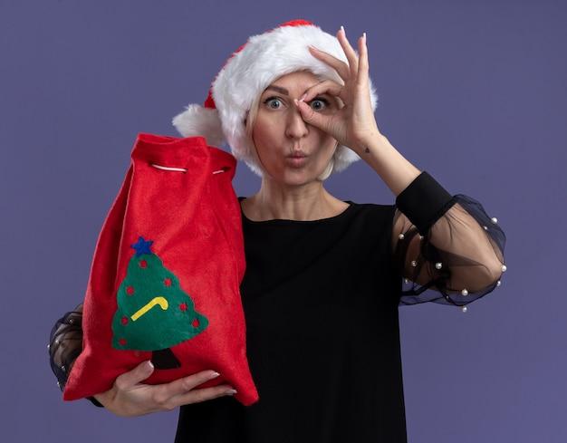 クリスマスの帽子をかぶって、紫色の背景に分離された口すぼめ呼吸でカメラを見てカメラを見て、クリスマスの帽子をかぶっている印象的な中年のブロンドの女性