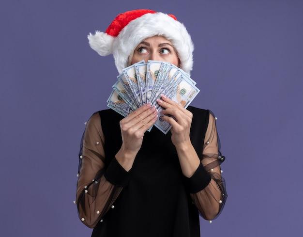 Impressionato donna bionda di mezza età che indossa il cappello di natale che tiene i soldi guardando il lato da dietro isolato sulla parete viola con lo spazio della copia