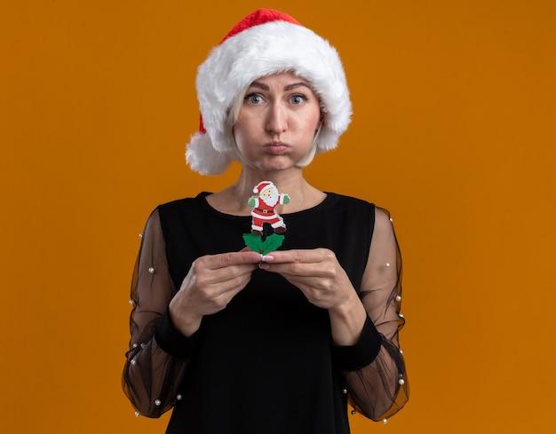 오렌지 배경에 고립 된 산타 클로스 장난감 퍼핑 뺨을 들고 카메라를보고 크리스마스 모자를 쓰고 감동 중년 금발의 여자