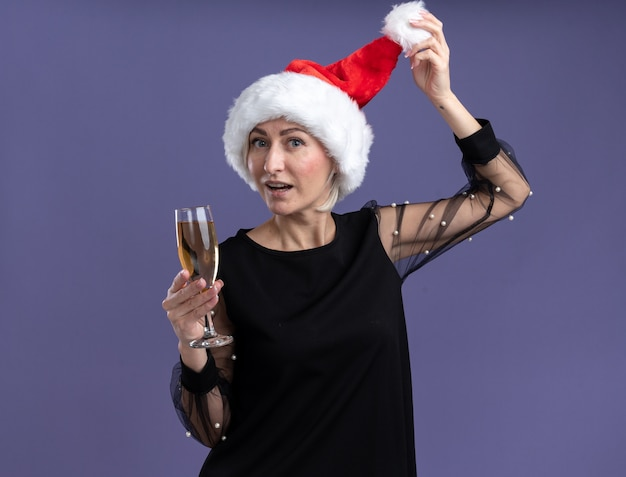 Impressed middle-aged blonde woman wearing christmas hat looking at camera holding glass of champagne grabbing hat isolated on purple background