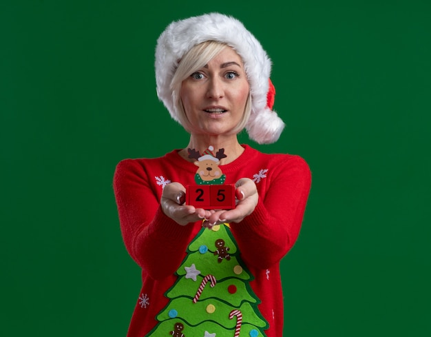 Impressed middle-aged blonde woman wearing christmas hat and sweater stretching out christmas reindeer toy with date towards camera looking at camera isolated on green background