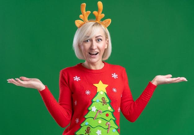 녹색 배경에 고립 된 빈 손을 보여주는 카메라를보고 크리스마스 순록 뿔 머리띠와 크리스마스 스웨터를 입고 감동 중년 금발의 여자
