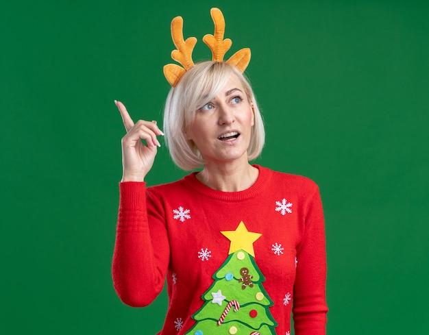 녹색 배경에 고립 가리키는 측면에서 찾고 크리스마스 순록 뿔 머리띠와 크리스마스 스웨터를 입고 감동 중년 금발의 여자
