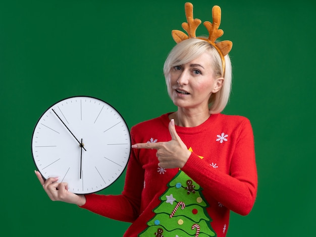 Impressed middle-aged blonde woman wearing christmas reindeer antlers headband and christmas sweater holding and pointing at clock looking at camera isolated on green background