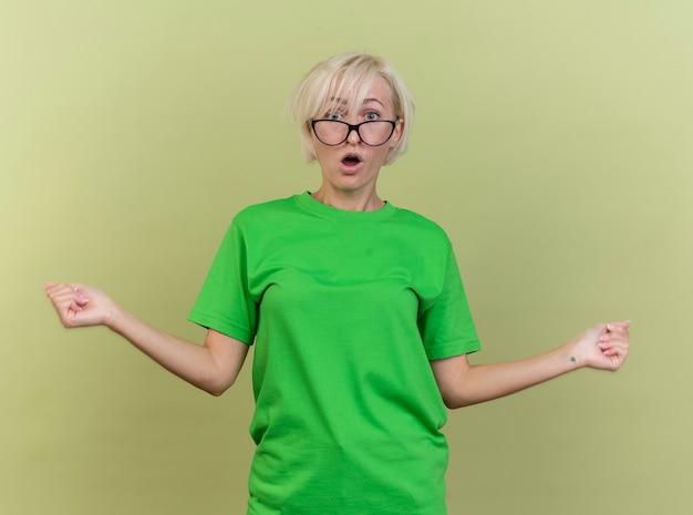 オリーブグリーンの壁に隔離された拳を伸ばして正面を見て眼鏡をかけている印象的な中年のブロンドの女性