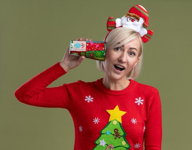 Впечатленная блондинка средних лет в головной повязке санта-клауса и рождественском свитере держит пластиковую рождественскую чашку рядом с ухом и смотрит, слушая разговор, изолирована на оливково-зеленой стене