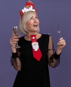 サンタクロースのヘッドバンドとネクタイを身に着けている印象的な中年のブロンドの女性は、紫色の背景で隔離の休日の線香花火とシャンパングラスを見上げています