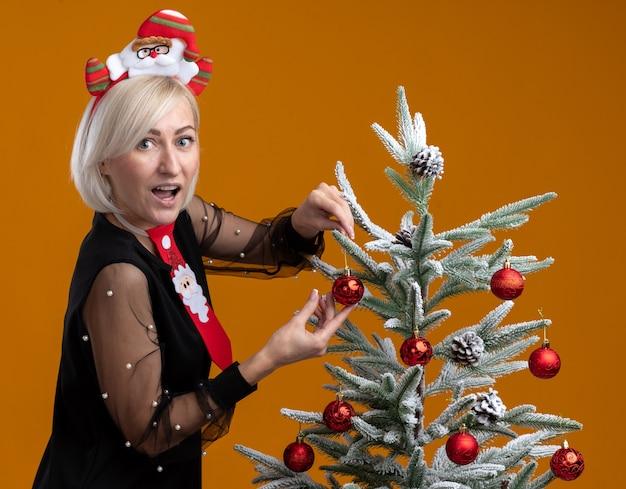 Впечатленная блондинка средних лет в повязке на голову санта-клауса и галстуке, стоящая в профиль возле елки, украшающая ее елочными шарами, выглядящая изолированной на оранжевой стене