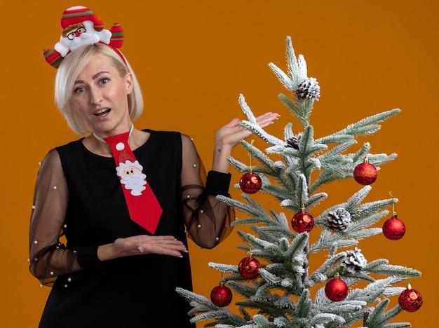 オレンジ色の背景に分離されたカメラを見て手でそれを指している装飾されたクリスマスツリーの近くに立っているサンタクロースのヘッドバンドとネクタイを身に着けている印象的な中年のブロンドの女性