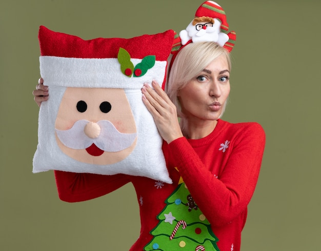 Impressed middle-aged blonde woman wearing santa claus headband and christmas sweater holding santa claus pillow touching head with it looking  with pursed lips isolated on olive green wall