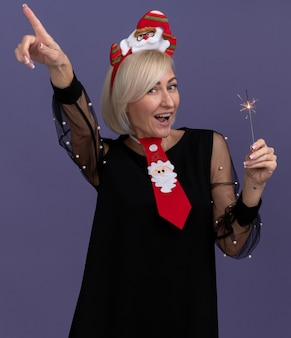 Impressed middle-aged blonde woman wearing santa claus headband and tie holding holiday sparkler looking at camera pointing up isolated on purple background