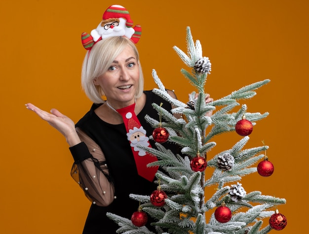 Impressed middle-aged blonde woman wearing santa claus headband and tie standing behind decorated christmas tree touching it looking at camera showing empty hand isolated on orange background