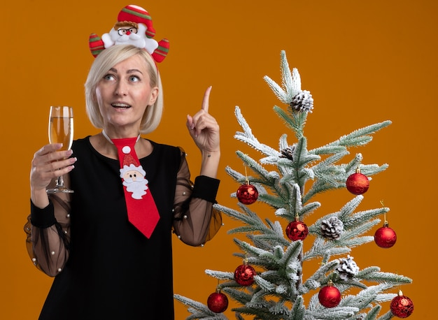 Impressed middle-aged blonde woman wearing santa claus headband and tie standing near decorated christmas tree holding glass of champagne looking and pointing up isolated on orange background