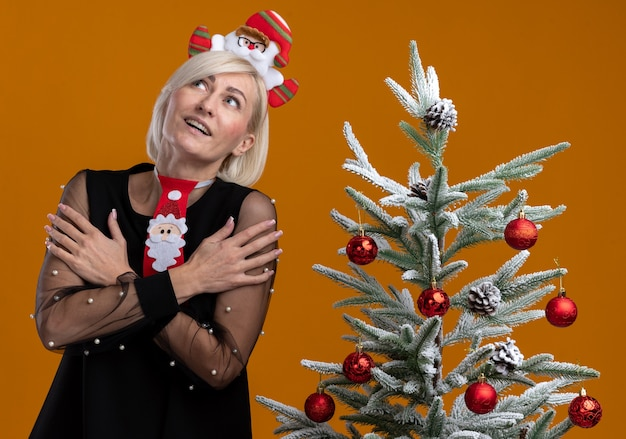 Impressed middle-aged blonde woman wearing santa claus headband and tie standing near decorated christmas tree keeping hands crossed on arms looking up isolated on orange background