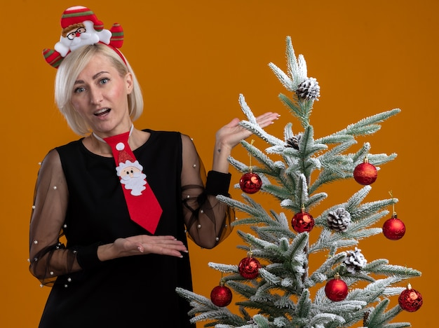 Impressed middle-aged blonde woman wearing santa claus headband and tie standing near decorated christmas tree pointing at it with hands looking at camera isolated on orange background