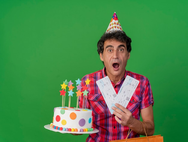 Impressed middle-aged caucasian party man wearing birthday cap holding birthday cake paper bag and airplane tickets looking at camera isolated on green background with copy space
