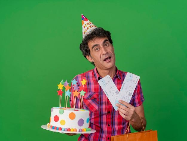 コピースペースで緑の背景に分離されたカメラを見てバースデーケーキの紙袋と飛行機のチケットを保持しているバースデーキャップを身に着けている印象的な中年の白人パーティーの男