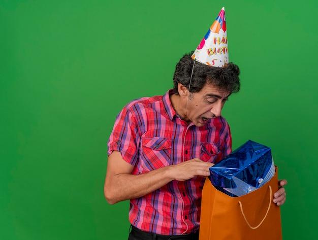 Impressionato uomo caucasico di mezza età del partito che indossa il cappello di compleanno guardando all'interno del sacchetto di carta con confezione regalo isolato su sfondo verde con spazio di copia