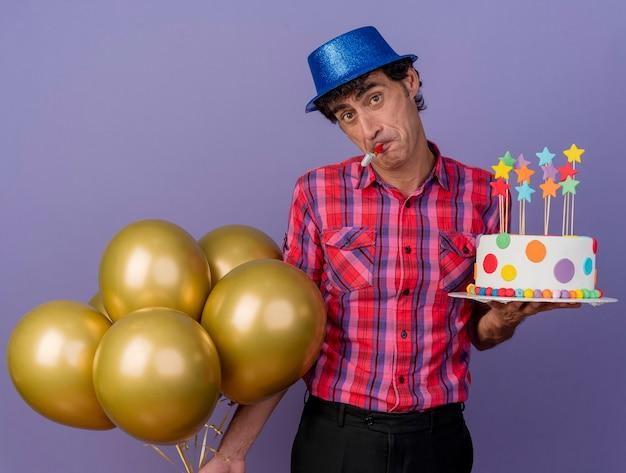 Impressionato uomo caucasico di mezza età che indossa il cappello del partito che tiene palloncini e torta di compleanno con ventilatore di partito in bocca che guarda l'obbiettivo isolato su priorità bassa viola