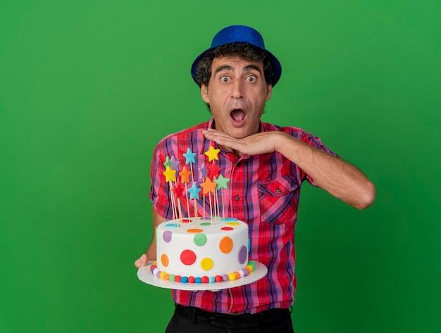 Impressionato uomo caucasico di mezza età del partito che indossa il cappello del partito che tiene la torta di compleanno che tiene la mano sotto il mento che guarda l'obbiettivo isolato su priorità bassa verde con lo spazio della copia