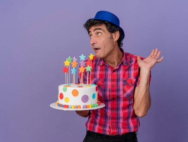 Impressionato uomo caucasico di mezza età del partito che indossa il cappello del partito che tiene la torta di compleanno che osserva in su che mostra la mano vuota isolata su fondo viola con lo spazio della copia