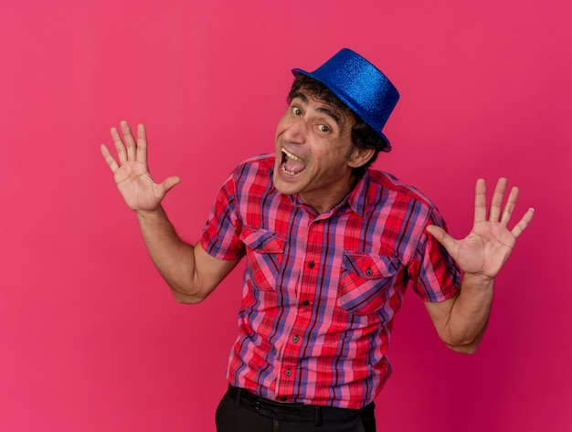Impressed middle-aged caucasian party man wearing party hat looking at camera showing empty hands isolated on crimson background