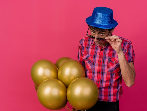 Impressed middle-aged caucasian party man wearing party hat and sunglasses holding balloons grabbing glasses looking at camera isolated on crimson background with copy space