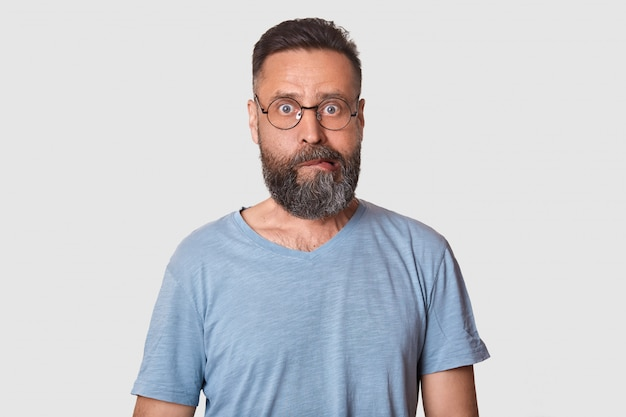 Impressed middle aged curious man with black beard has strange facial expression