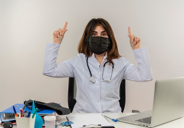 Medico femminile di mezza età impressionato che porta mascherina medica che si siede allo scrittorio con la lavagna per appunti degli strumenti medici ed il computer portatile che indica in su isolato