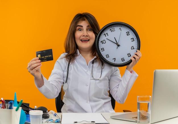 의료 가운과 청진기를 착용하고 의료 도구 클립 보드와 노트북 시계와 신용 카드를 들고 책상에 앉아 감동 된 중년 여성 의사
