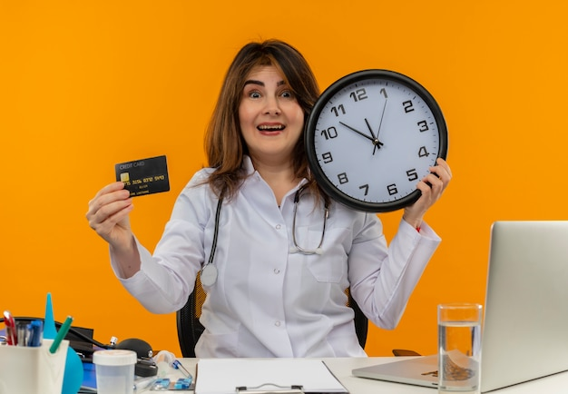 Impressed middle-aged female doctor wearing medical robe and stethoscope sitting at desk with medical tools clipboard and laptop holding clock and credit card isolated